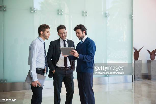 businessman presenting idea to associates using digital tablet - tres personas fotografías e imágenes de stock