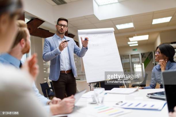 businessman presenting new project to partners in the office - demonstration stock pictures, royalty-free photos & images