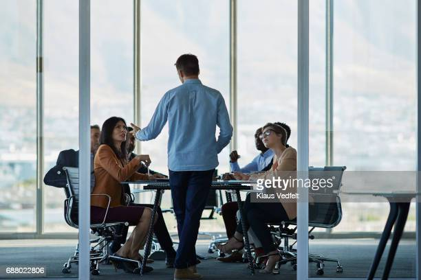 Businessman presenting plan in large meeting room
