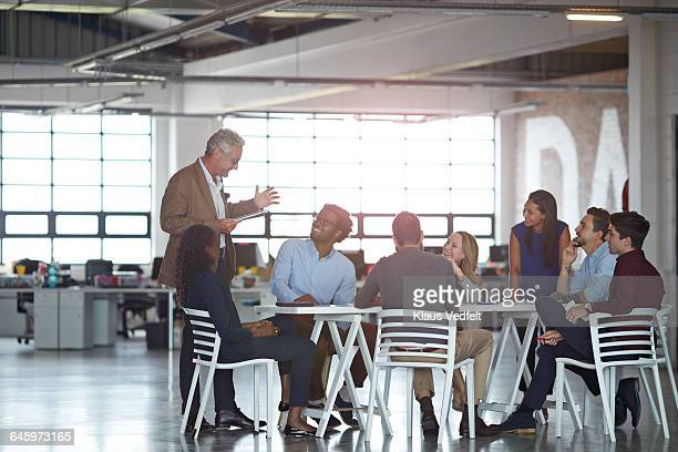 Businessman presenting project, in big open office