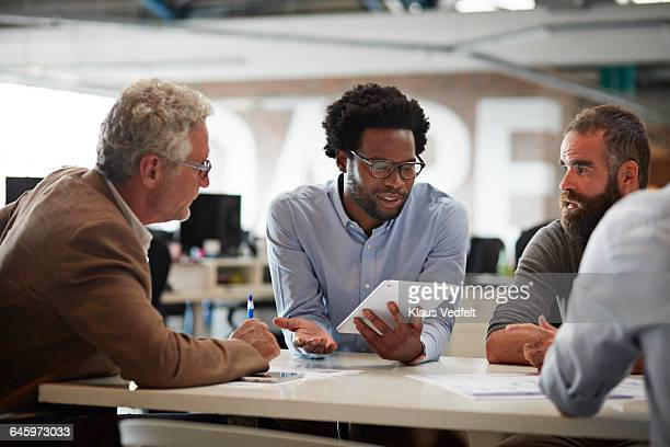 Businessman presenting to co-workers with tablet