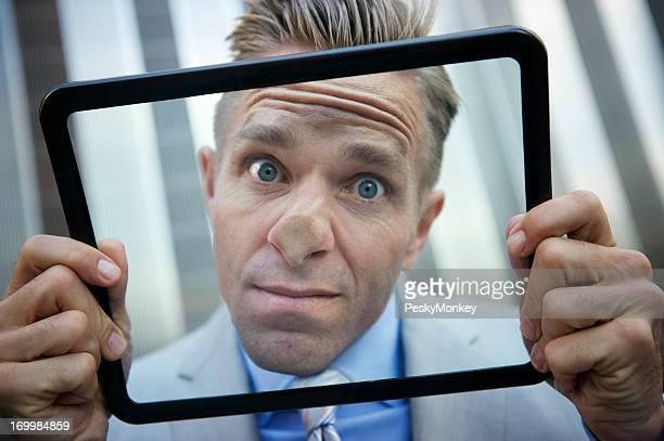 Businessman Presses His Nose Against Tablet Computer