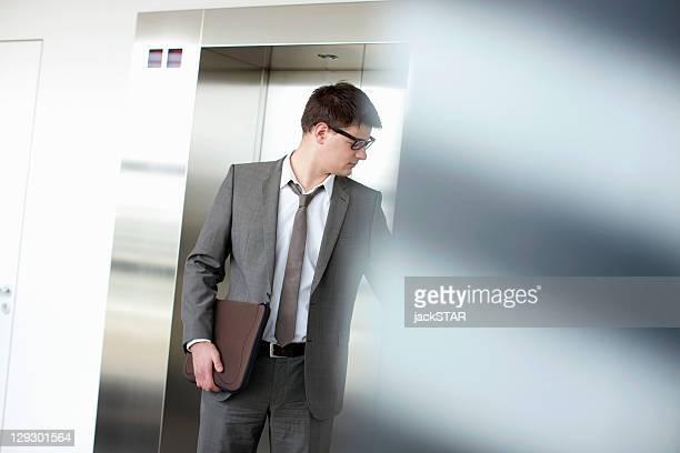 Businessman pressing elevator button