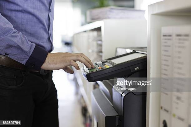 Businessman pressing the start button to print.