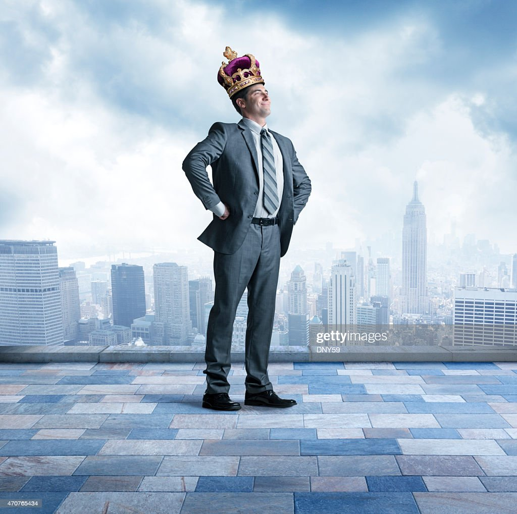 Businessman proudly wearing a crown above big city skyline : Stock Photo
