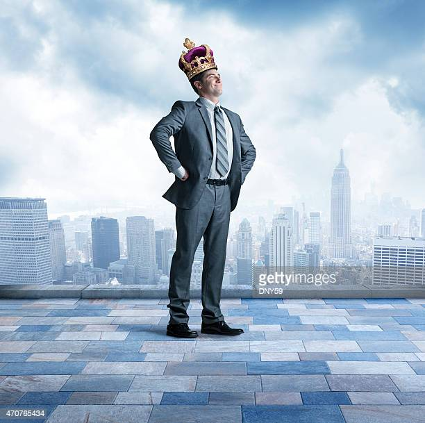 businessman proudly wearing a crown above big city skyline - koning koninklijk persoon stockfoto's en -beelden