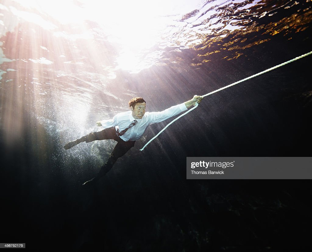 Businessman pulled by rope underwater : Stock Photo