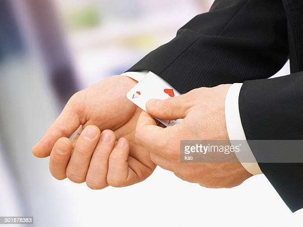 businessman pulling an ace out of his sleeve - sleeve stock photos and pictures