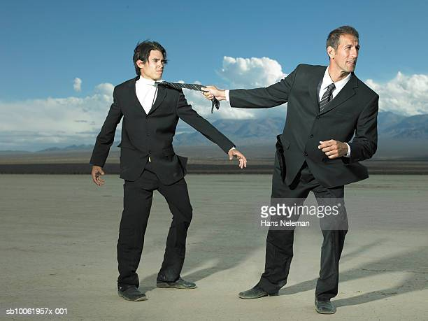 Businessman pulling another businessman by in desert