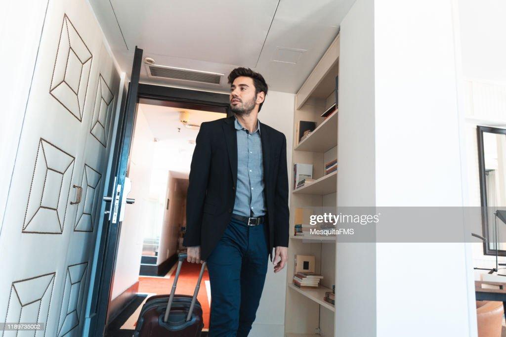 ビジネスマンは彼の荷物を引っ張り、ホテルの部屋に入ります : ストックフォト