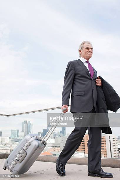 businessman pulling luggage across urban balcony - wheeled luggage stock photos and pictures