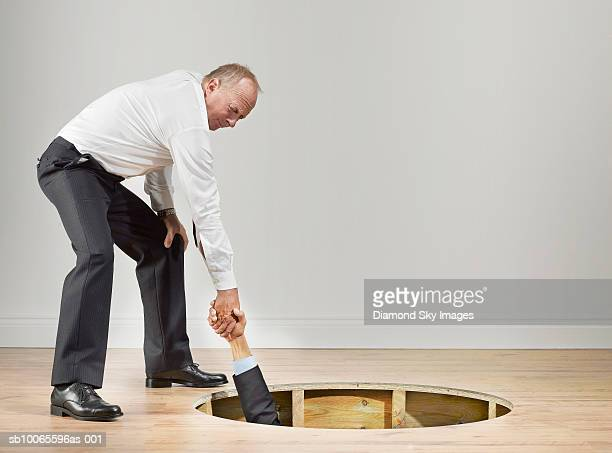 businessman pulling man out from hole of wooden floor - hole stock photos and pictures