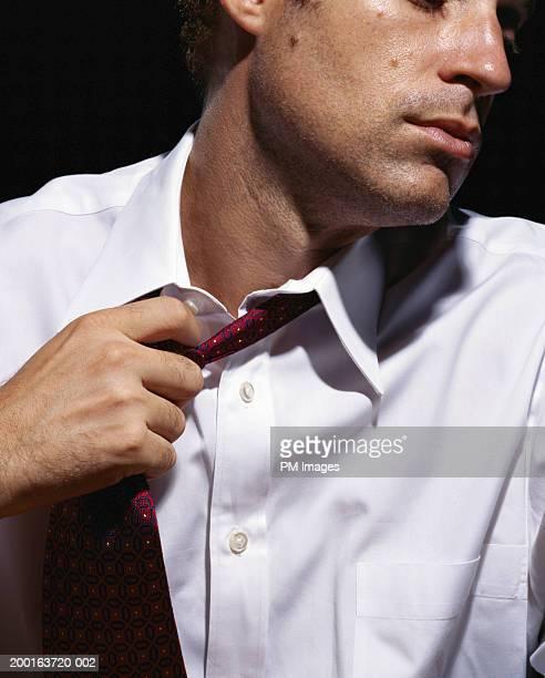 Businessman pulling off tie