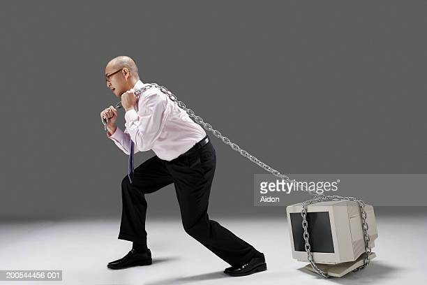 businessman pulling old technology with chain, studio shot - dragging stock pictures, royalty-free photos & images