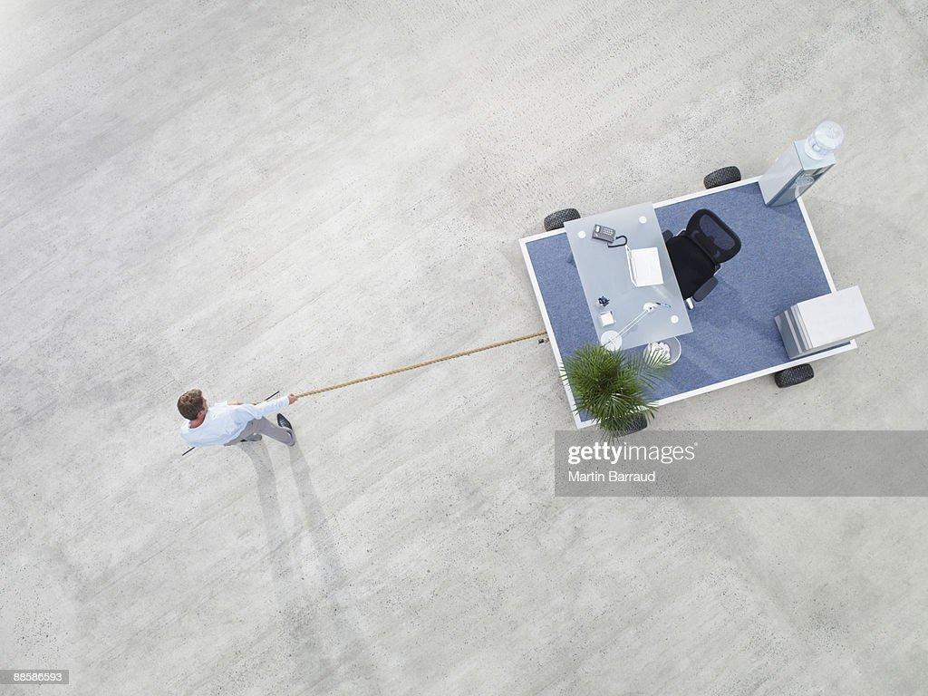 Businessman pulling portable office : Bildbanksbilder