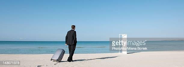 Businessman pulling suitcase on beach, walking towards half-open door
