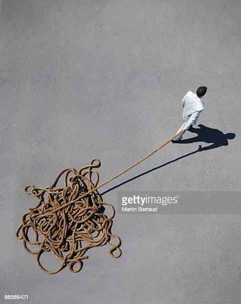 Businessman pulling tangled rope