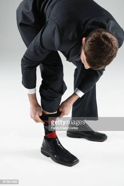 Businessman pulling up socks