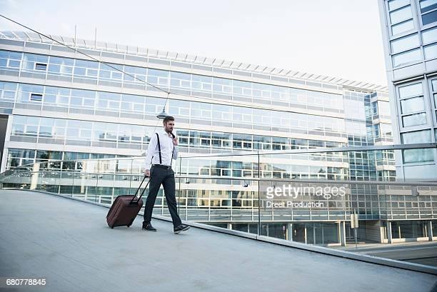 Businessman pulling wheeled luggage on footbridge, Munich, Bavaria, Germany