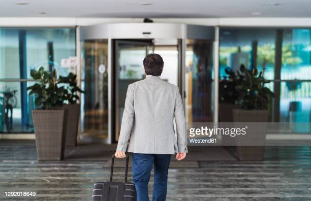 businessman pulling wheeled luggage while leaving hotel - building entrance stock pictures, royalty-free photos & images