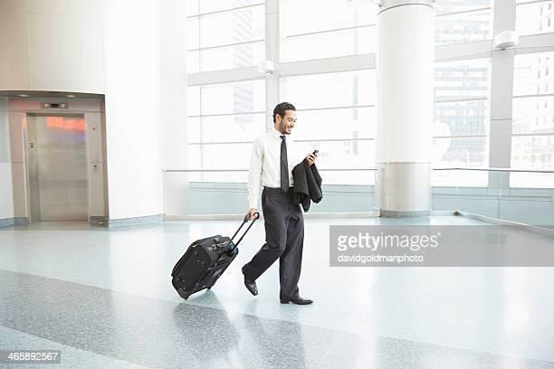 Businessman pulling wheeled suitcase