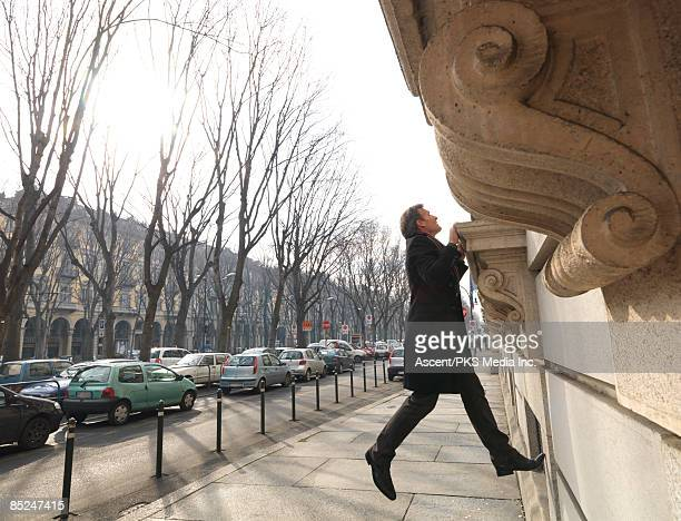 businessman pulls up window ledge to peer inside - peer to peer stock pictures, royalty-free photos & images