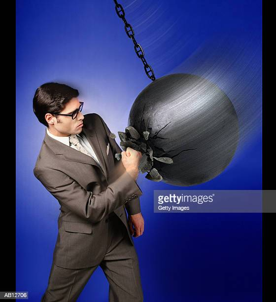 Businessman punching into demolition ball as it swings by