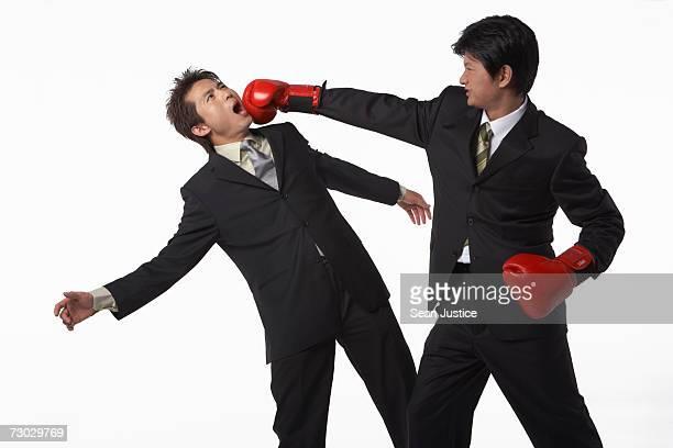 Businessman punching other businessman