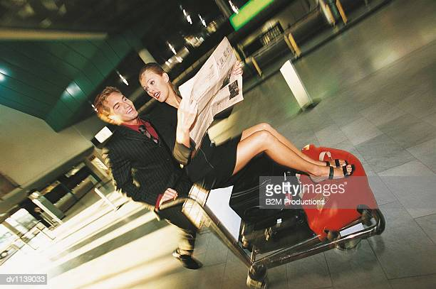 Businessman Pushing a Baggage Trolley in an Airport Concourse With a Businesswoman Sitting in it Holding a Newspaper and Chatting to Him