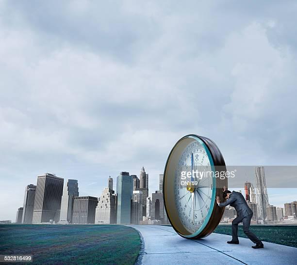 Businessman Pushing A Compass