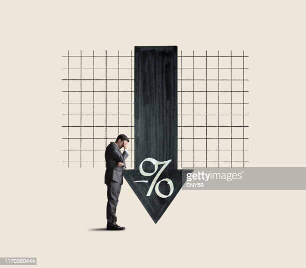 businessman pushing back against negative interest rates - sinal de percentagem imagens e fotografias de stock