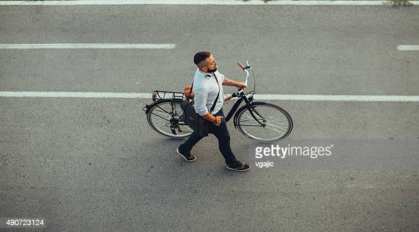 Businessman Pushing Bicycle and going home late.
