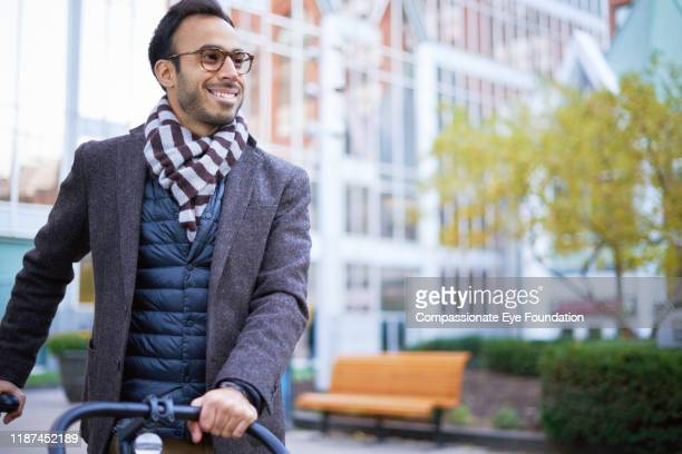 """businessman pushing bicycle in city - """"compassionate eye"""" stock pictures, royalty-free photos & images"""