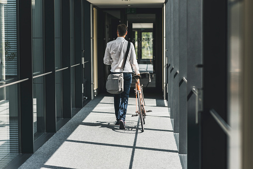 Businessman pushing bicycle in office passageway - gettyimageskorea