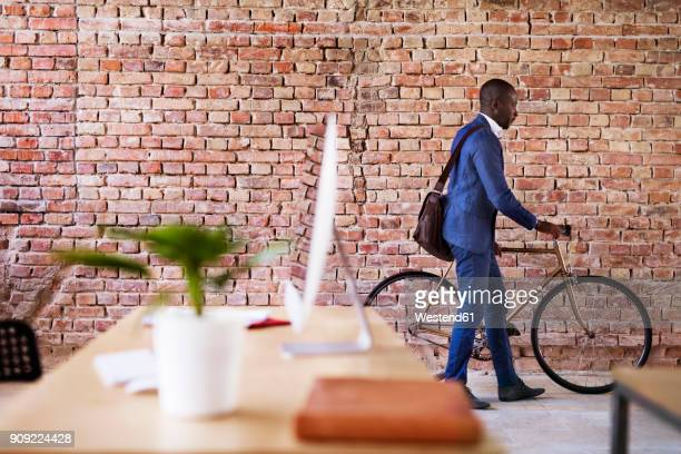 businessman pushing bicycle in office - ショルダーバッグ ストックフォトと画像