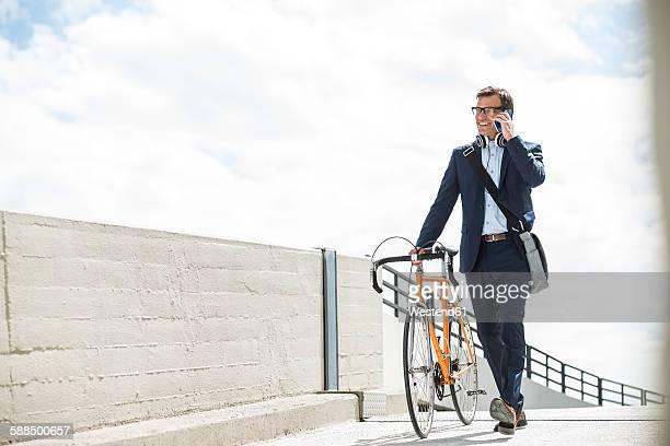 businessman pushing bike while talking on the phone - draagbaarheid stockfoto's en -beelden
