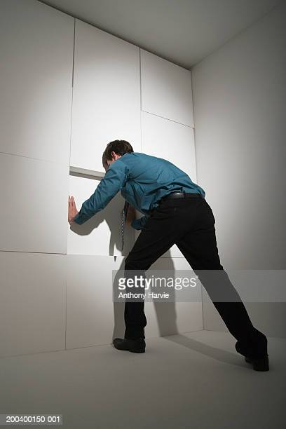 Businessman pushing block in wall, rear view