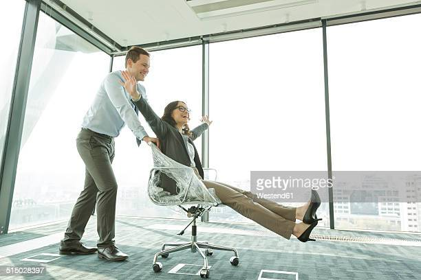 Businessman pushing businesswoman in office chair