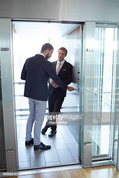 Businessman pushing button in elevator