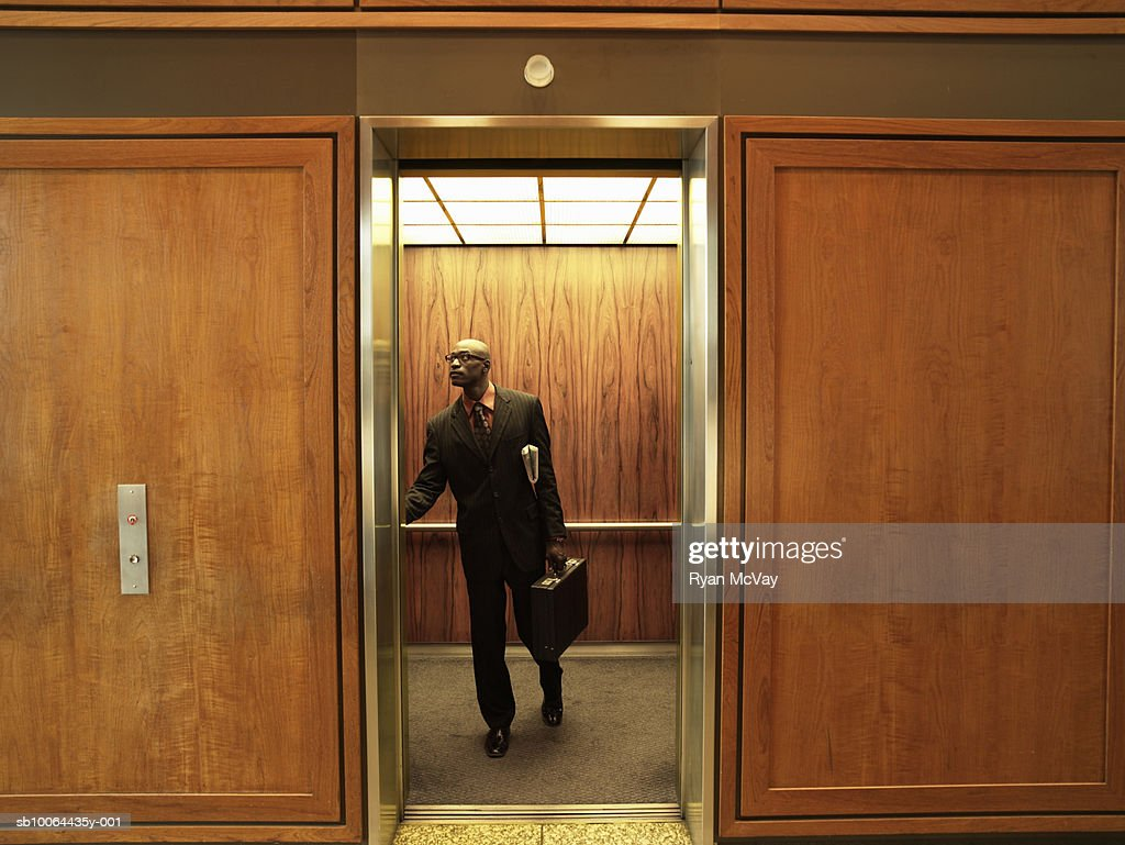Businessman pushing button inside elevator : Stock Photo