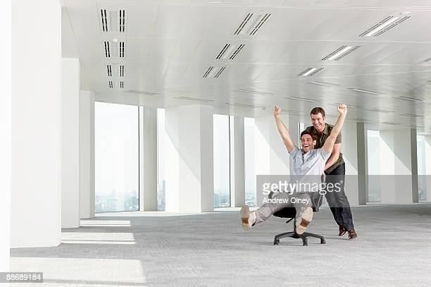 Businessman pushing co-worker in chair in empty office