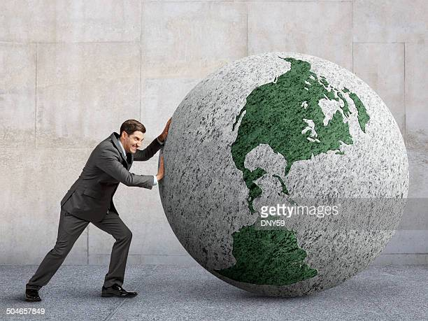 Businessman Pushing Globe Rotated Towards North America