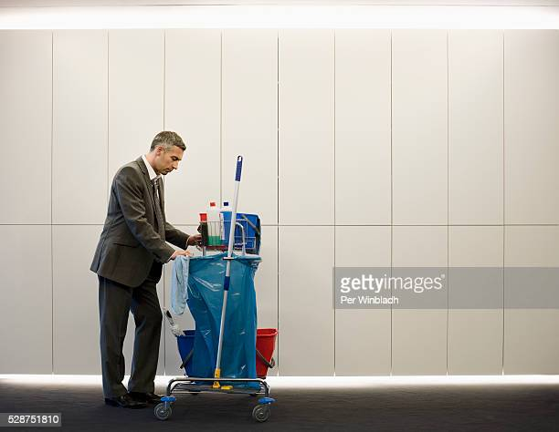 Businessman pushing janitorial cart