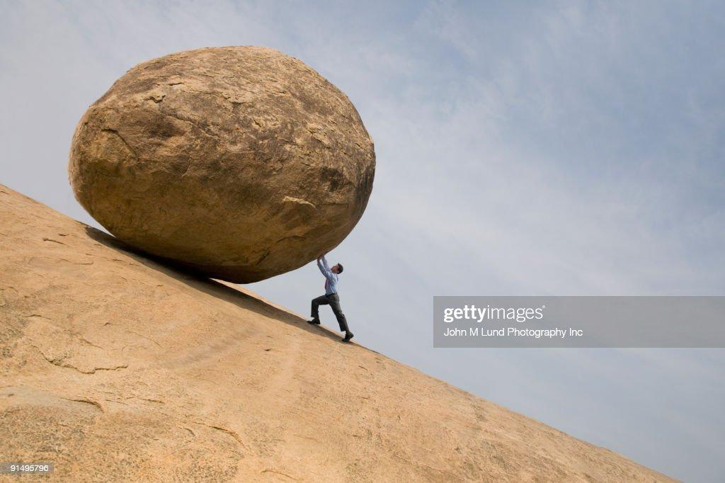Businessman pushing large rock uphill : Stock Photo