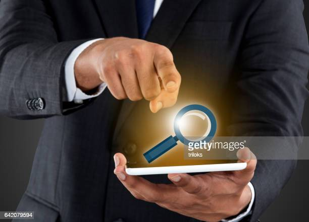 Businessman pushing magnifying virtual button