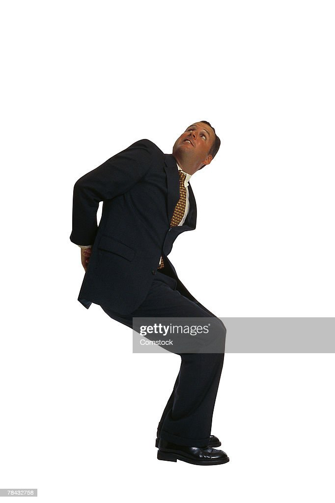 Businessman pushing with his back : Stockfoto