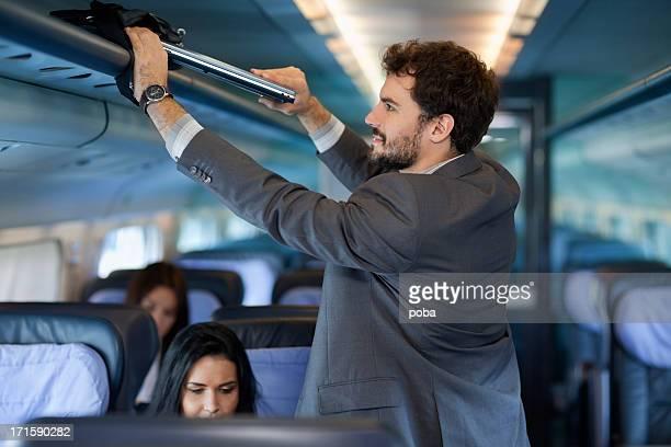 businessman  put  computer bag  on overhead luggage racks