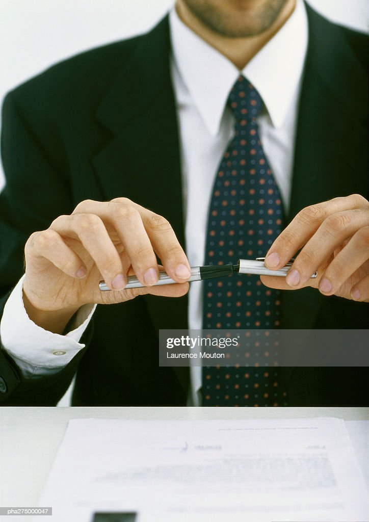 Businessman putting cap on pen, partial view : Stockfoto