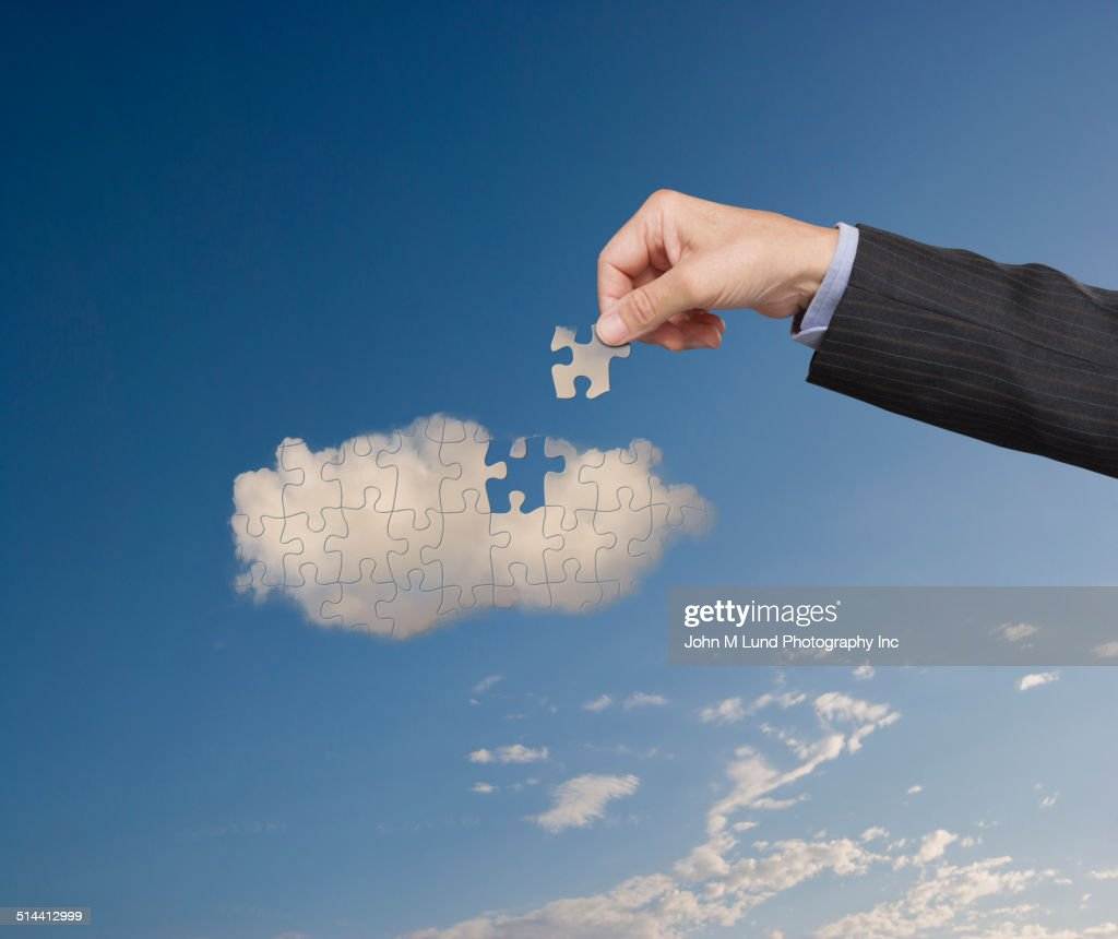 Businessman putting cloud puzzle together : Stock Photo