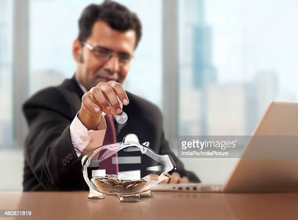 Businessman putting coin in piggy bank at office desk
